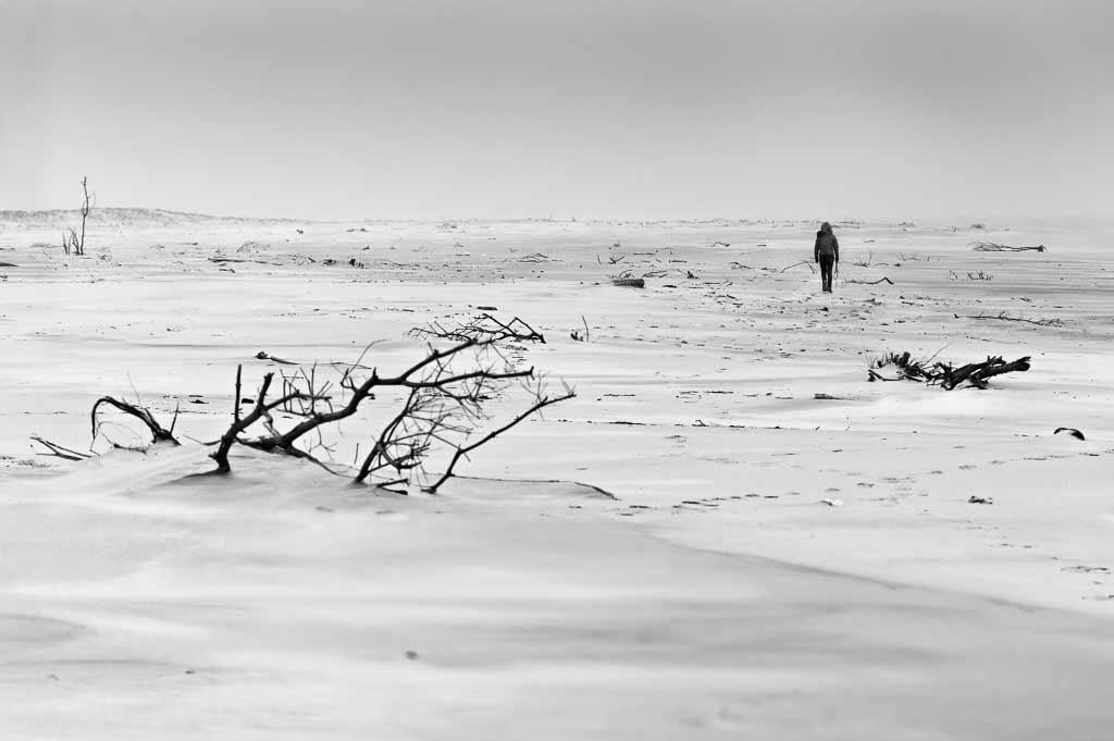 une jeune fille dans un desert de sable sur la Plage de la pointe de grave - Gironde - février 2020