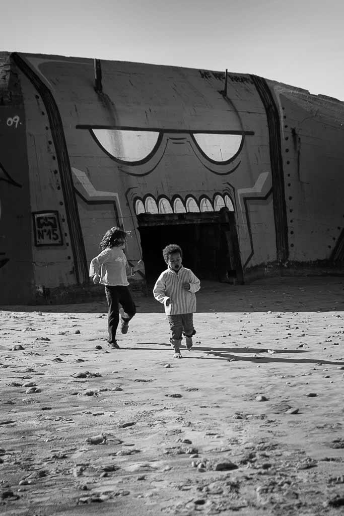 2 enfants courent devant la grande bouche peinte sur un Blockhaus Montalivet