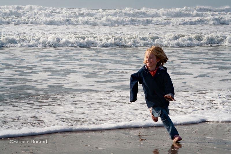 Une petite fille joue avec les vagues