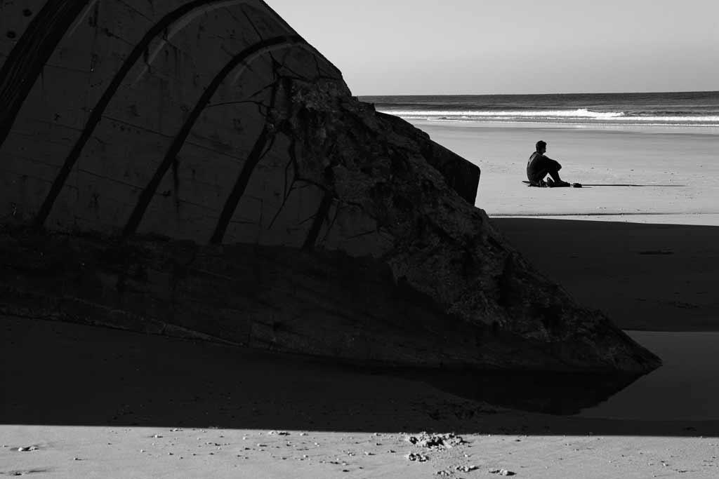 Surfeur face à la mer devant un blockhaus. Montalivet.