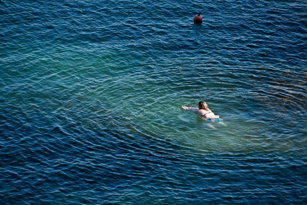 Une femme nage seul Cancale