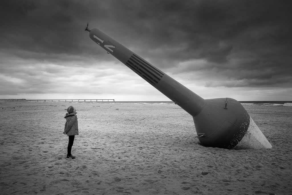 Une enfant face a une balise échouée sur la plage