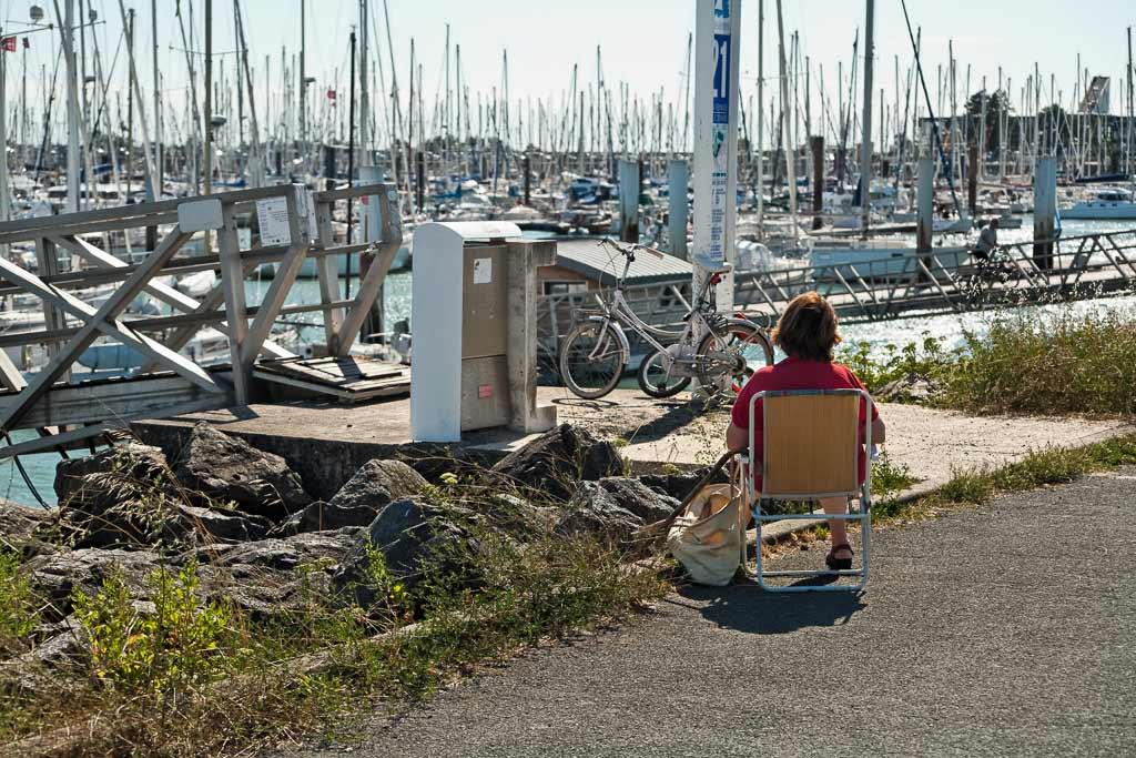 Une femme assise sur une chaise face au port des minimes La Rochelle