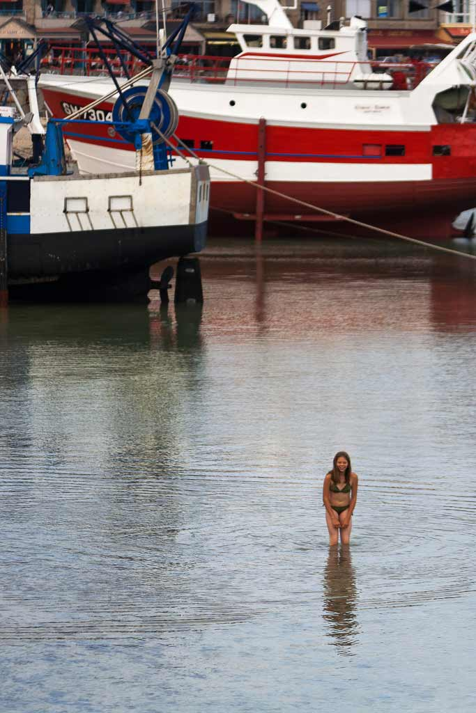 Jeune baigneuse au milieu des bateaux de pêche Cancale