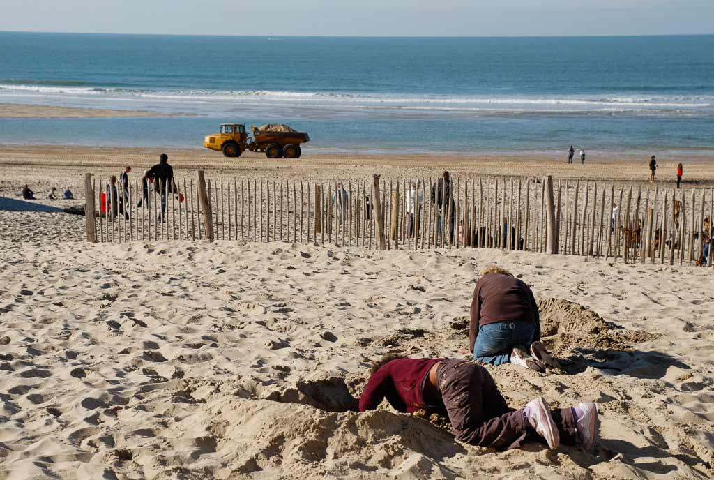 Un bulldoser passe et 2 enfants fond des troue dans le sable