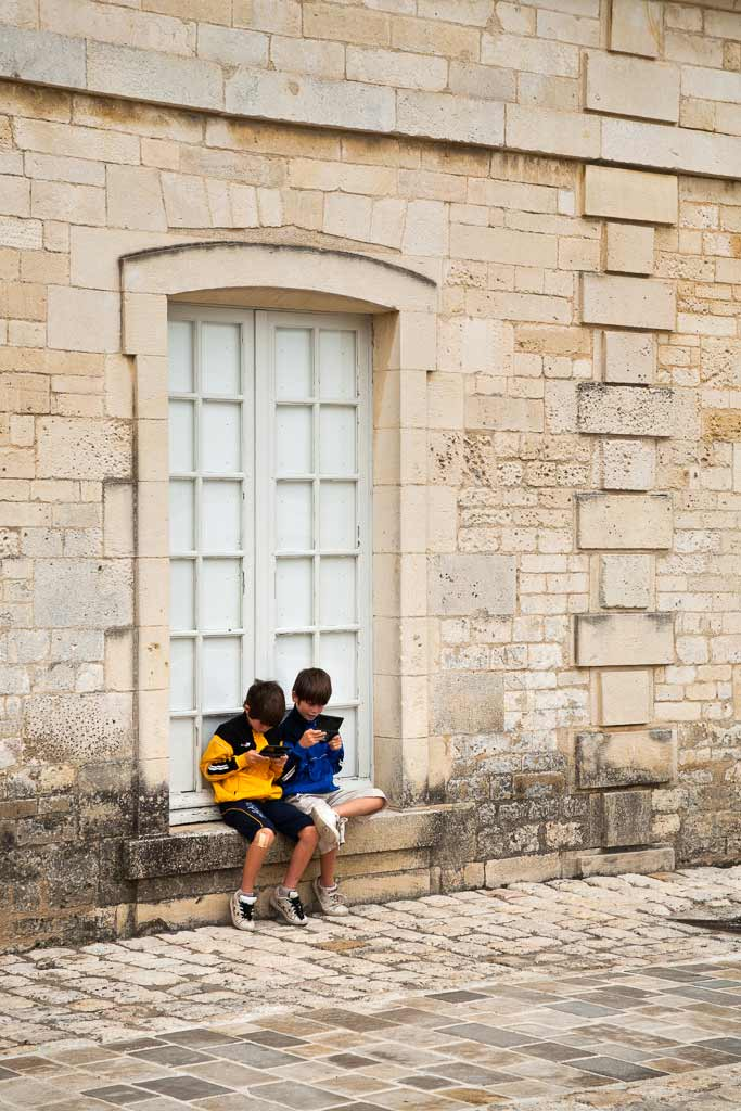 2 enfants joue sur leur console devant la Corderie Royale Rochefort