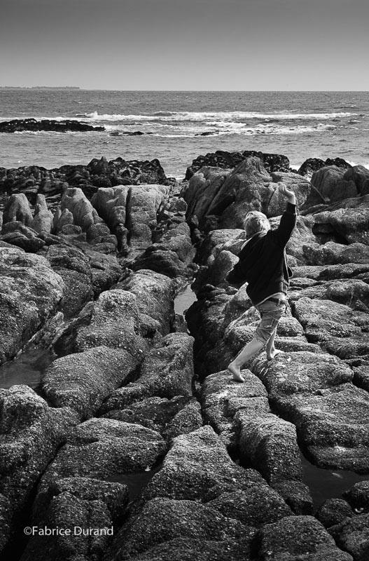 Un enfant joue sur les rochers Bretagne