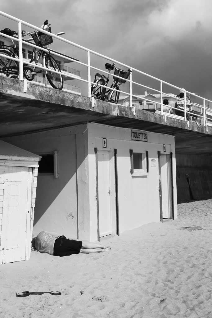 Une personne allongée a l'abri des toilettes plage du Croisic