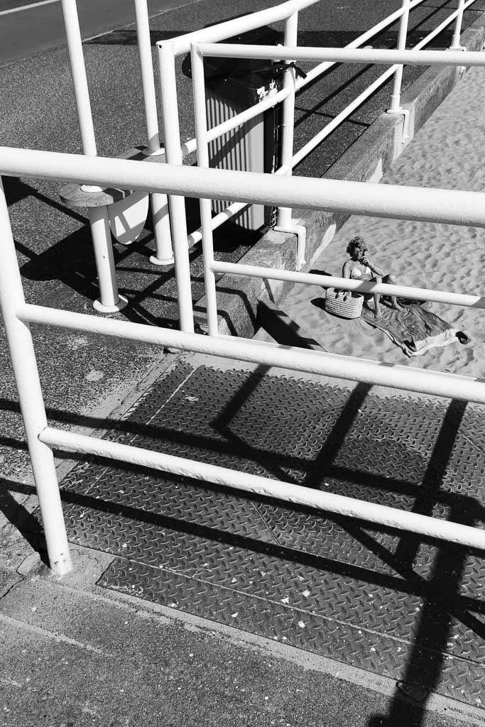Une femme à l'abri derrière les barrières de la plage du Croisic.