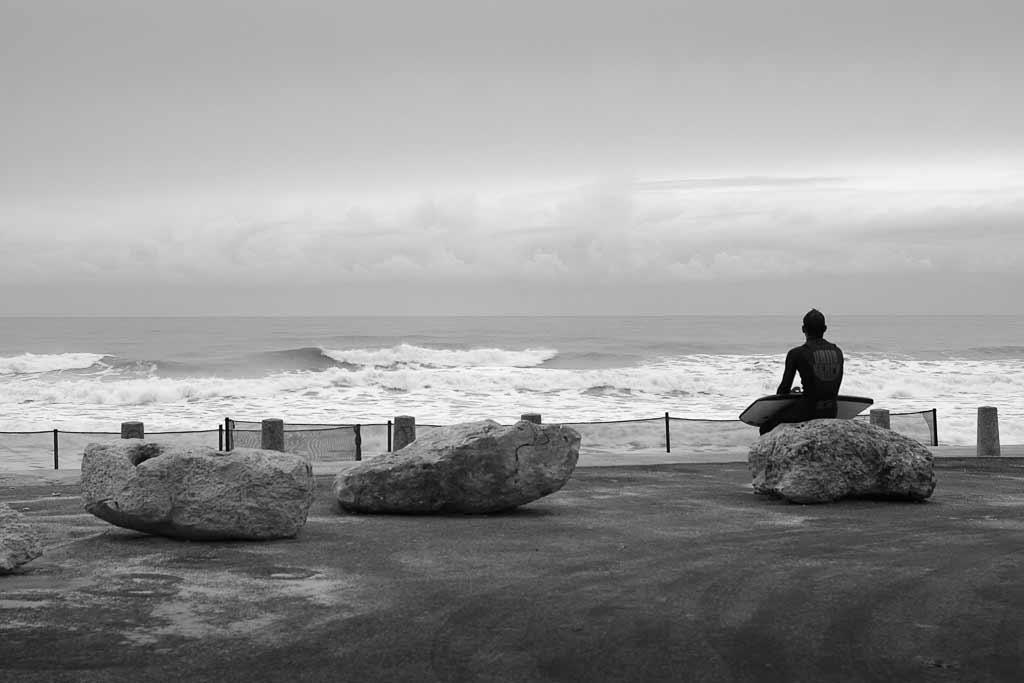 Seul assis sur un rocher un surfeur observe les vagues.