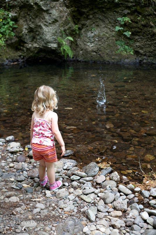 Une petite fille jette un caillou dans l'eau