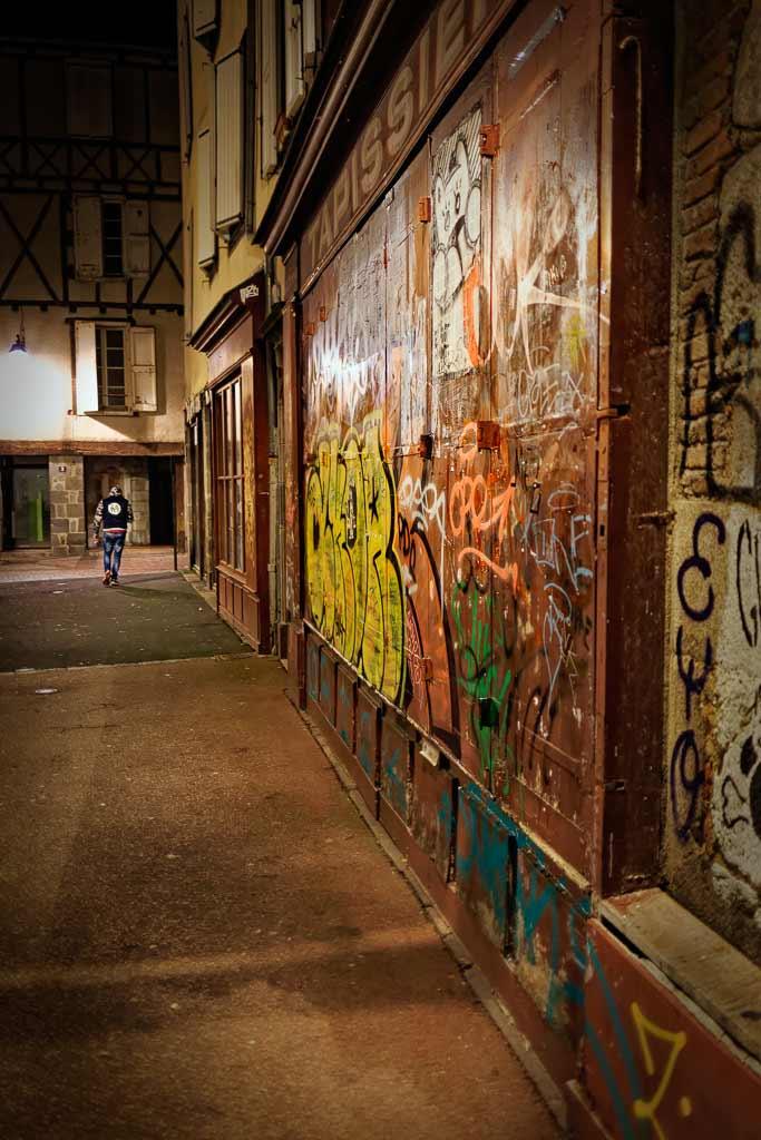 Un homme marche la nuit dans une vieille rue taguée Aurillac