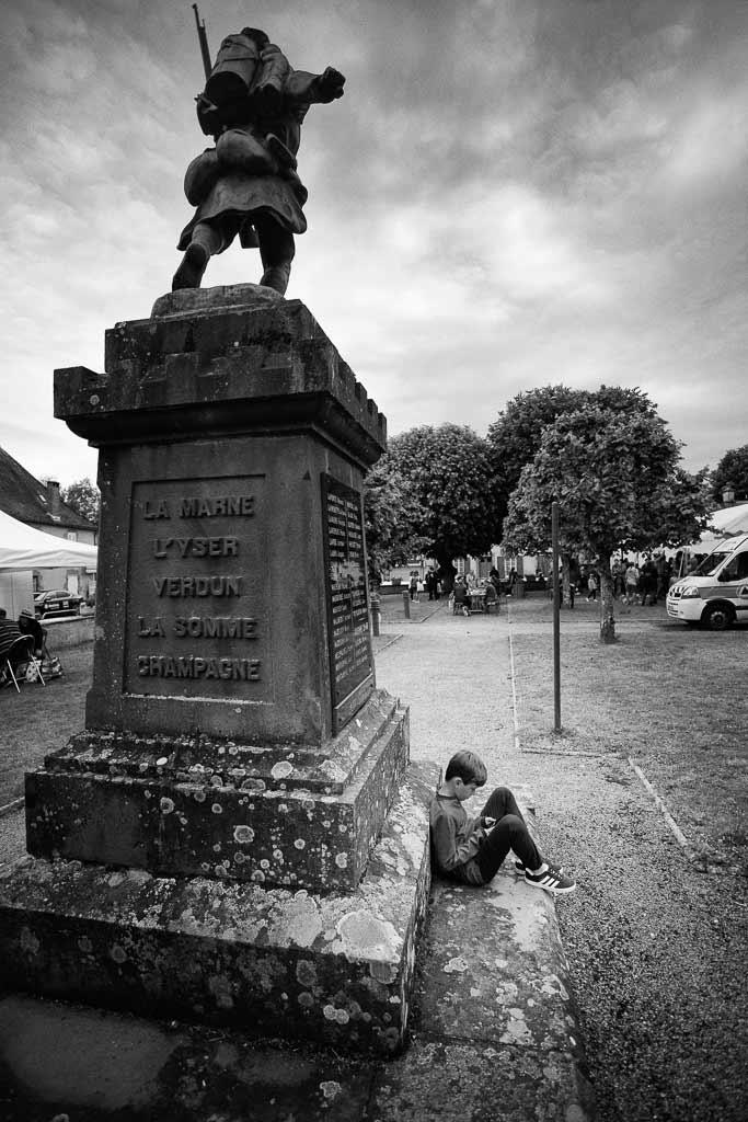 Un jeune garçon joue à la console de jeux assis contre le monument aux morts de Jussac