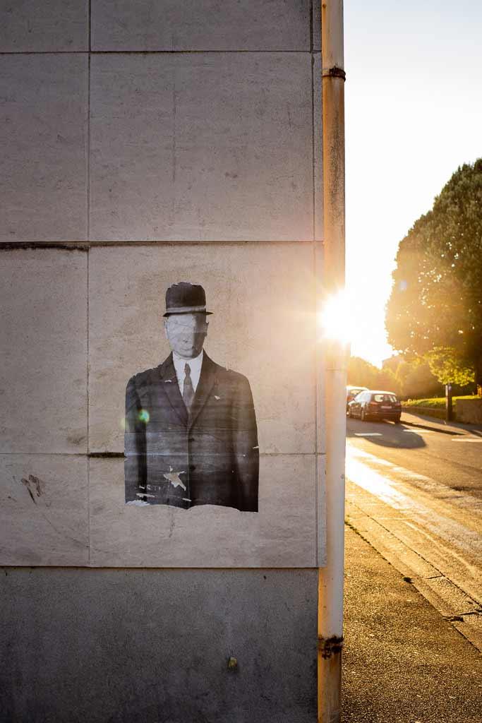 Collage murale d'un personnage a la Magritte Rochefort