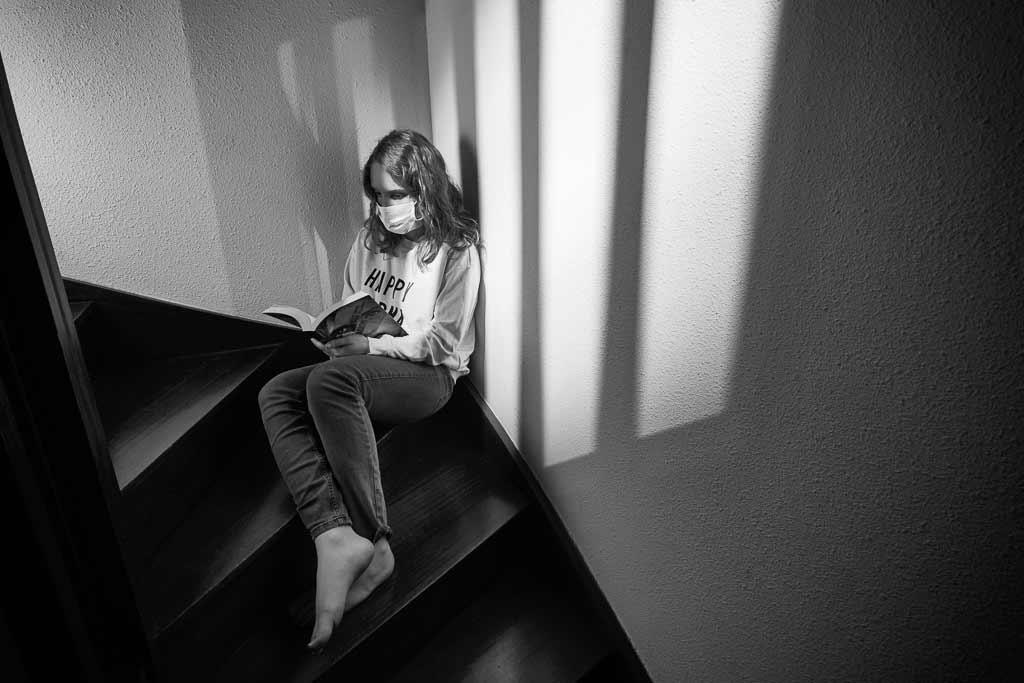 Portrait Jeune fille dans l'escalier portant un masque pandant le confinement du COVID19