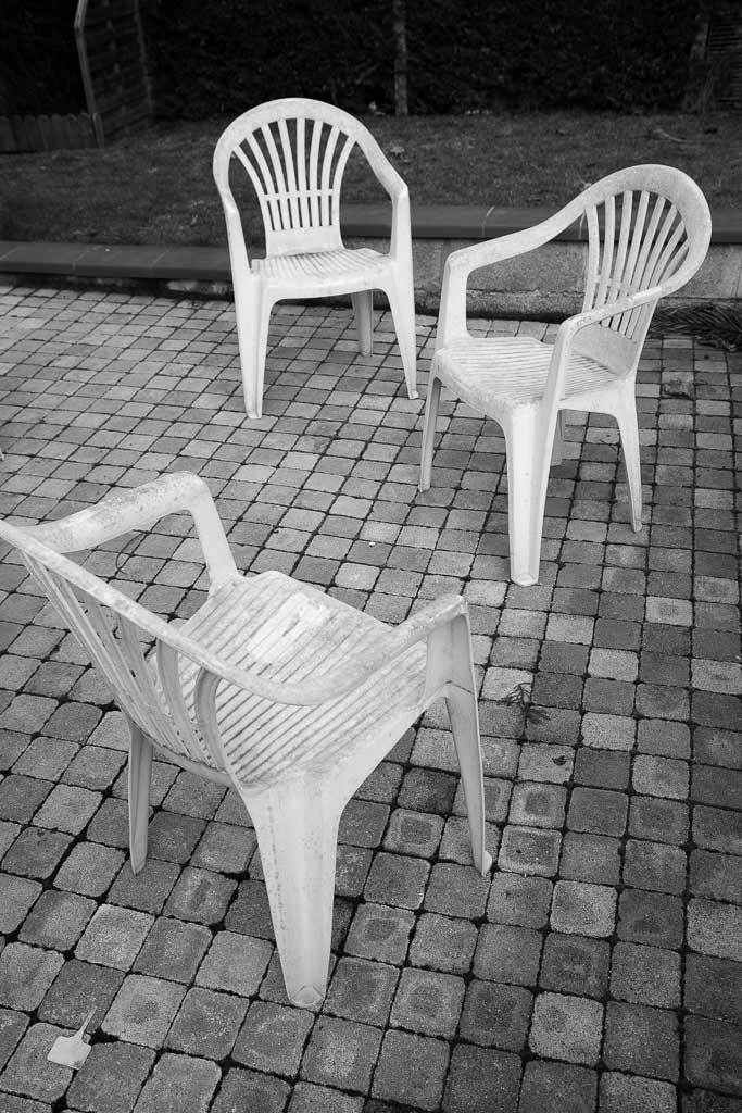 3 chaises plastique en pleine conversation sur la terrasse