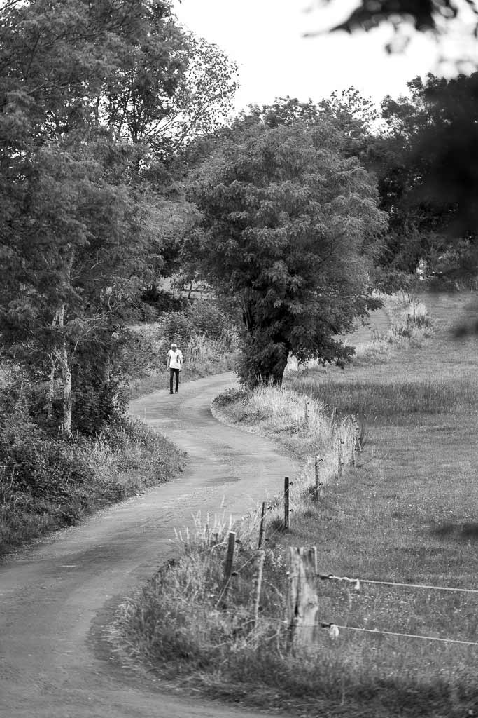 Un homme marche le long d'une route sinueuse