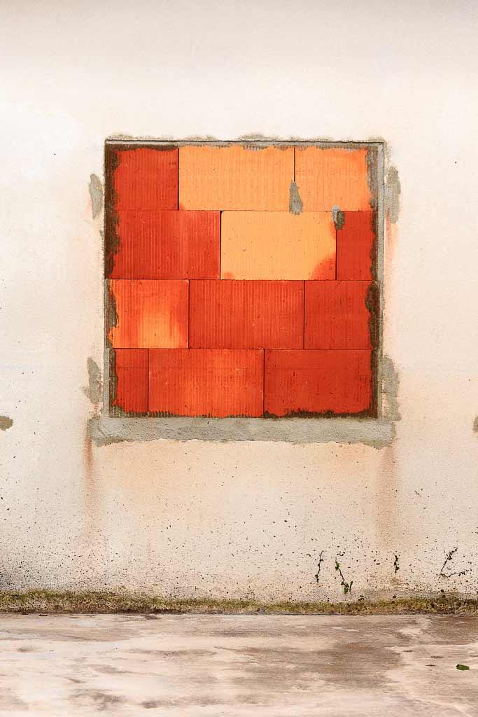 Fenêtre murée de briques rouges sur un mur blanc.